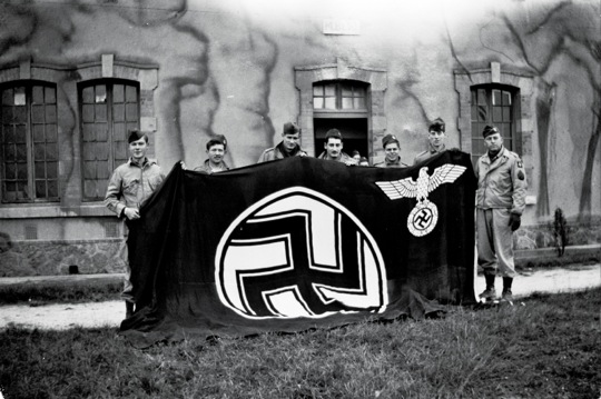 Tech/5 Brad Hinchliff (third from left) posing with captured German flag from the September 17th 1944 Holland combat jump.